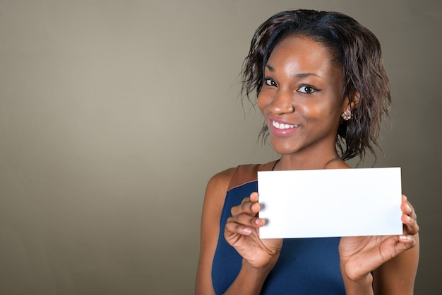 A beautiful woman with a perfect smile holds a card