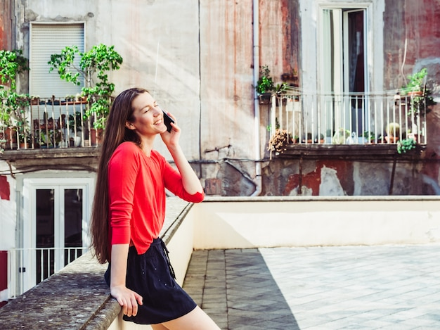 Beautiful woman with phone on the background of old houses