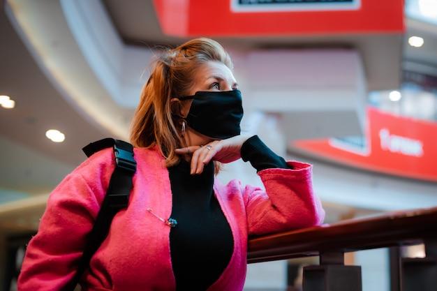 ウイルスに感染した空気から顔に黒い防護マスクが付いた電話明るいピンクのショッピングモールのコートを持つ美しい女性。