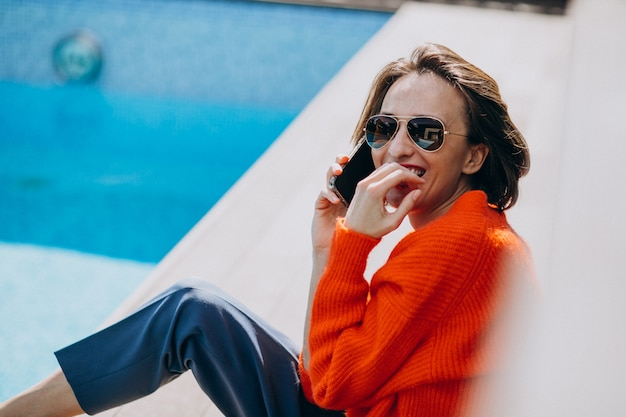 Красивая женщина с телефоном, сидя у бассейна
