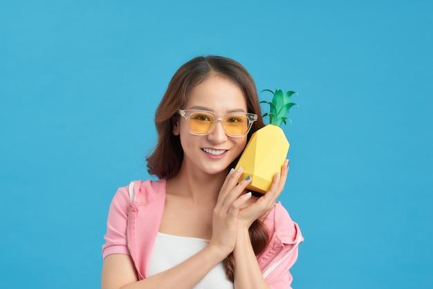 青い背景に分離されたパイナップルと美しい女性