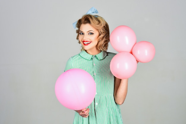 Beautiful woman with pink balloons on grey surface