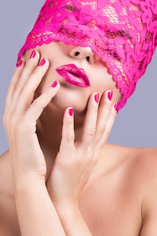 Beautiful woman with pink blindfold on her eyes