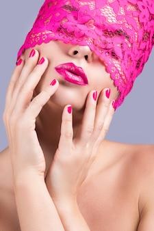 彼女の目にピンクの目隠しを持つ美しい女性