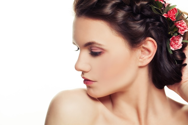 Beautiful woman with pink flowers in hairstyle. young beauty. brunette fashion model with makeup