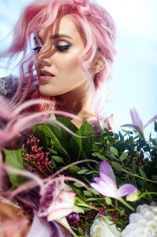 Beautiful woman with pink hair holds large bouquet with greenery and violet flowers