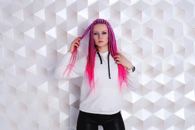 未来的な背景の上の白いパーカーのピンクの髪を持つ美しい女性。拡張現実ゲーム、未来のテクノロジー、aiコンセプト。 vr。