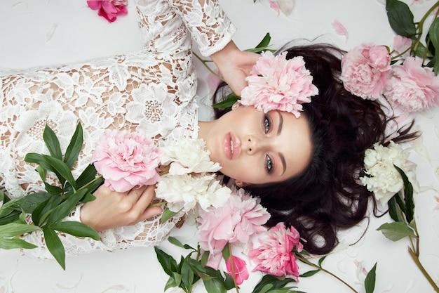 ピンクの牡丹の花を持つ美しい女性