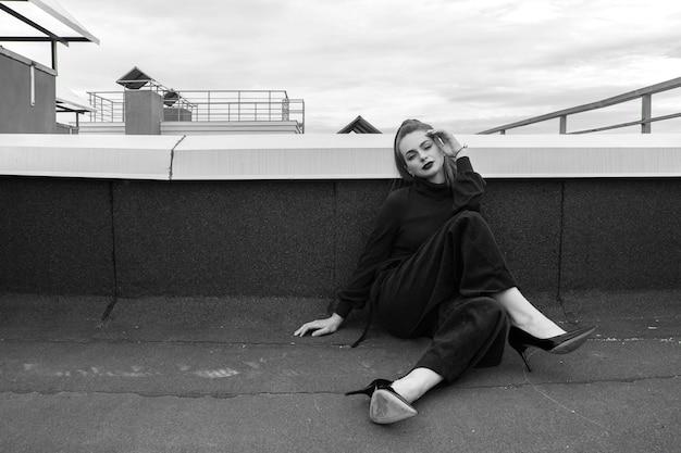 黒の衣装とパンプスで屋根の上に座っているポニーテールの美しい女性。黒と白。