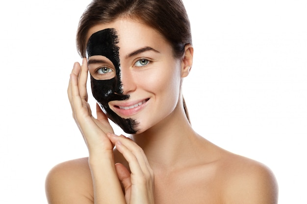 Beautiful woman with a purifying black mask on her face
