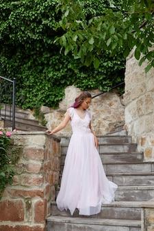 白いウェディングドレスを着た紫色の髪の美しい女性が庭を歩きます。ナチュラルメイク