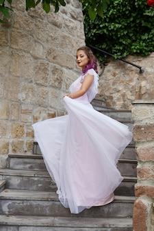 Красивая женщина с фиолетовыми волосами в белом свадебном платье гуляет в саду.