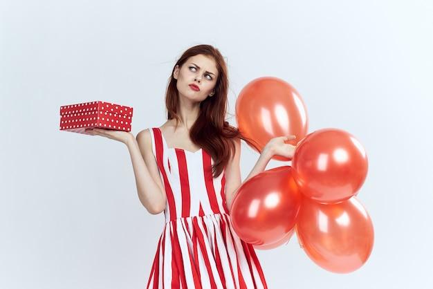 Красивая женщина с красными воздушными шарами и подарком