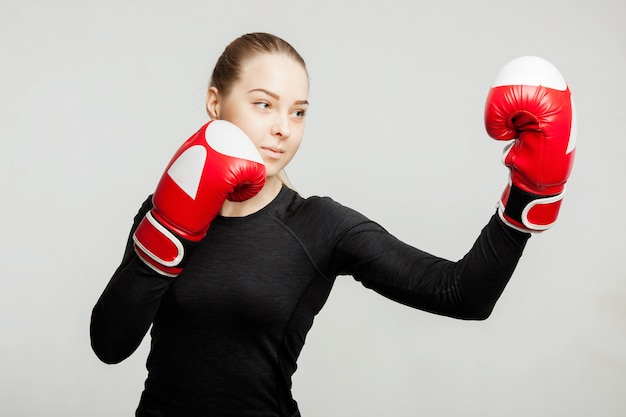 Beautiful woman with the red boxing gloves beats apercote attractive female boxer training.