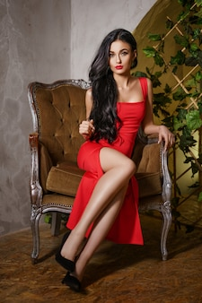 A beautiful woman with a red dress sits on a chair