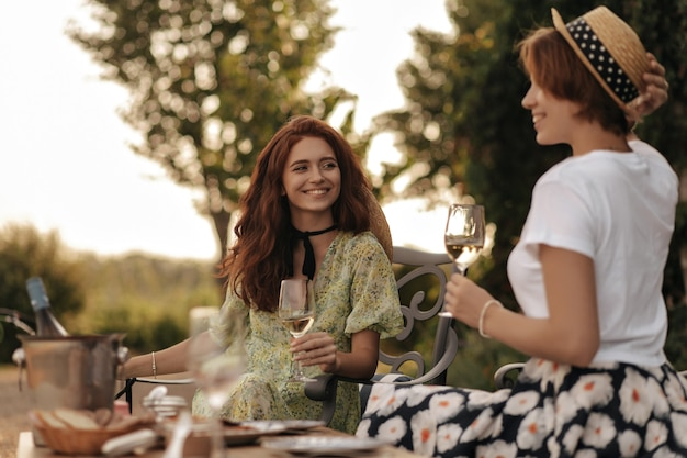 Beautiful woman with red hair in green dress smiling, holding glass and sitting with positive girl in t-shirt and skirt outdoor