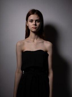 회색 벽에 검은 드레스에 붉은 머리를 가진 아름 다운 여자