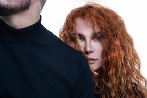 A beautiful woman with red hair stands behind the man's back. feelings and relationships in a couple. close-up.
