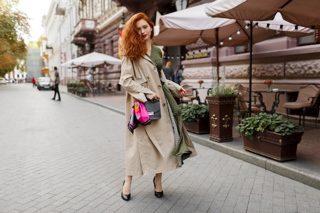 Beautiful woman with red hairs and bright make up walking on the street. wearing beige coat and green dress.