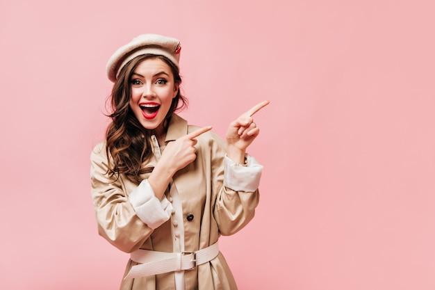 Bella donna con labbra rosse e occhi verdi guarda felicemente nella fotocamera e punta le dita a destra su sfondo isolato.