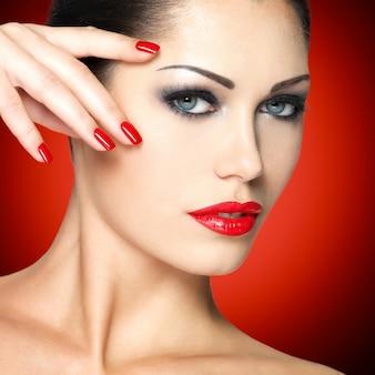 Bella donna con unghie rosse e trucco di moda