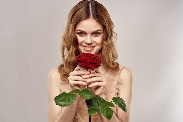 Красивая женщина с красной розой на стене светлого цвета
