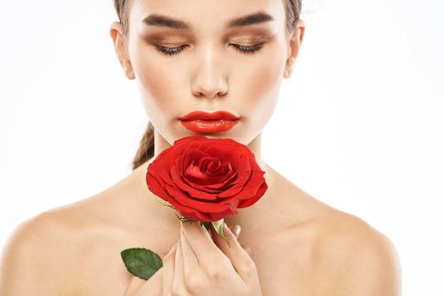 壁に向かってポーズをとって赤いバラの美しい女性