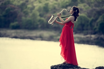 Beautiful woman with Saxophone Player Saxophonist playing jazz music
