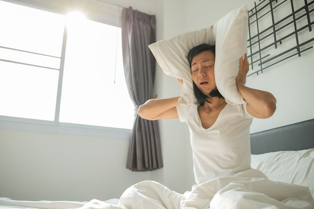 Beautiful woman with screams while sitting on the bed. young woman covers her ears with a pillow. headache from noise. annoyed adult woman suffering neighbour noise.