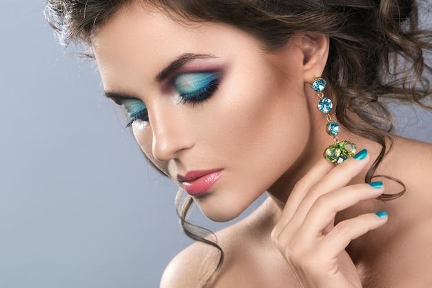 光沢のあるイヤリングを持つ美しい女性