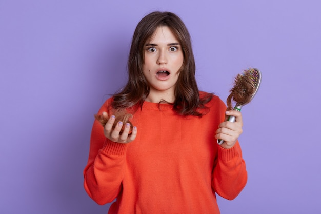 Beautiful woman with shocked facial expression, being upset of hair loss, needs treatment, holding comb with lots hair on it, wearing sweater, stands with opened mouth isolated over lilac wall.