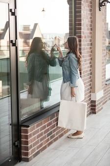 お店の窓を見て買い物袋を持つ美しい女性