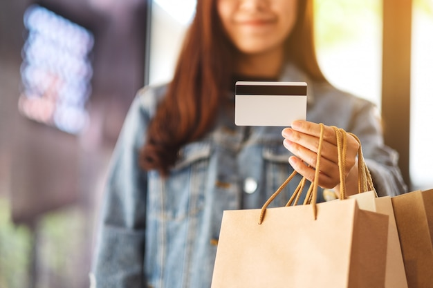 A beautiful woman with shopping bags holding and using a credit card for purchasing