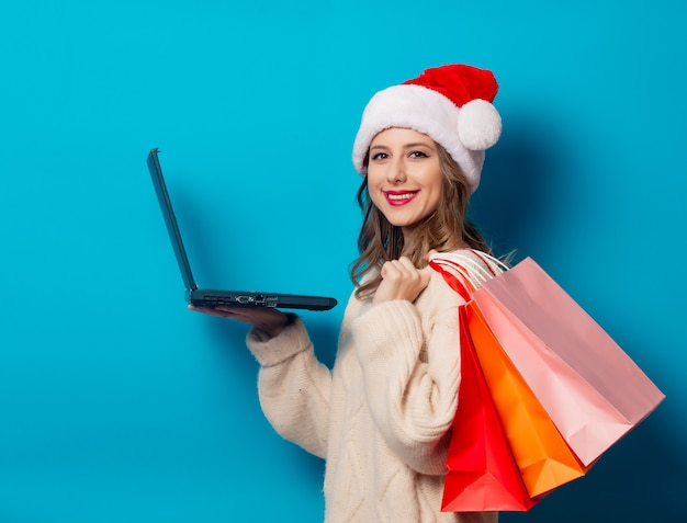 Beautiful woman with shopping bags and laptop computer on blue wall