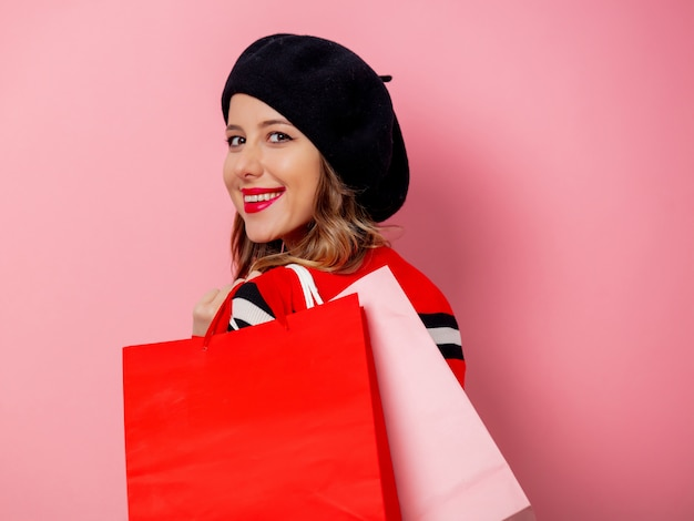 Beautiful woman with shopping bags on pink wall