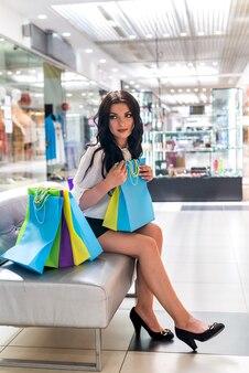 쇼핑몰에서 소파에 앉아 쇼핑 가방을 가진 아름 다운 여자