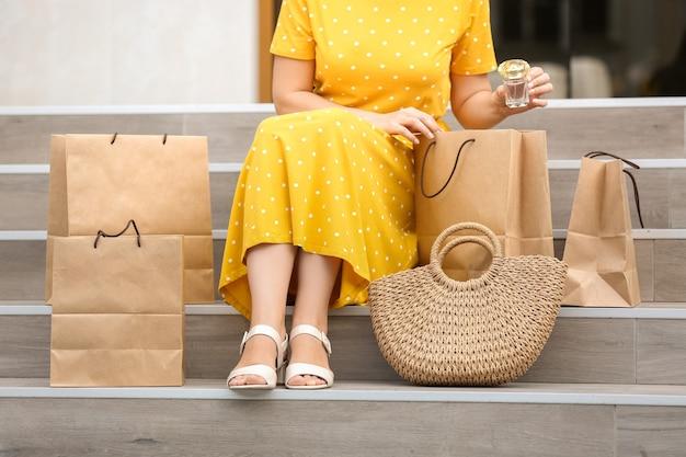야외 계단에 앉아 쇼핑백을 가진 아름 다운 여자