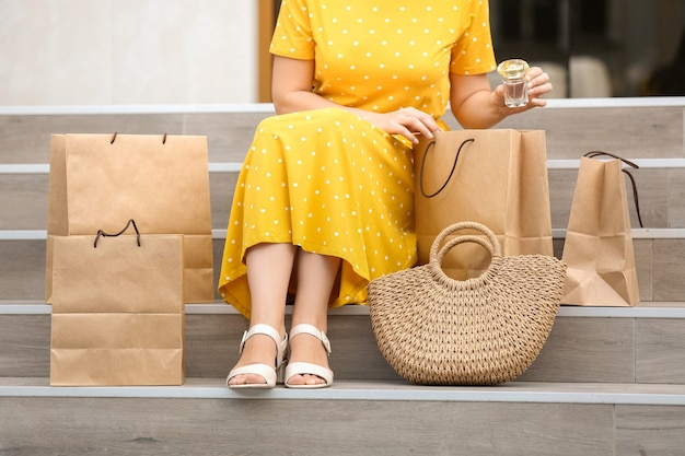Beautiful woman with shopping bags sitting on stairs outdoors