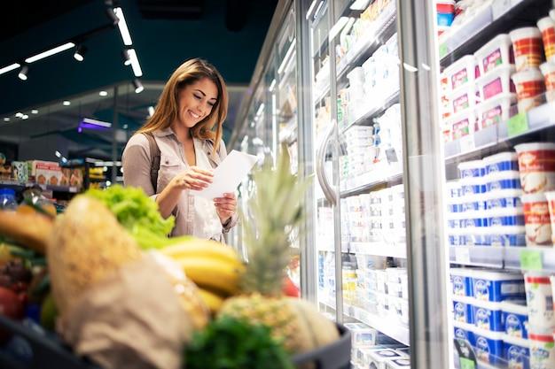 슈퍼마켓에서 음식을 사는 쇼핑 목록을 가진 아름 다운 여자