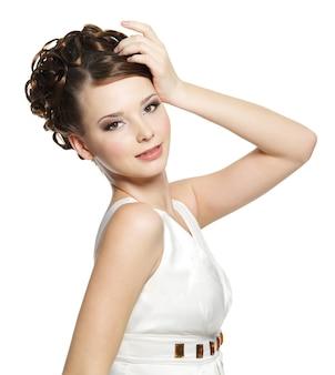 Bella donna con acconciatura riccia corta e trucco marrone degli occhi su bianco