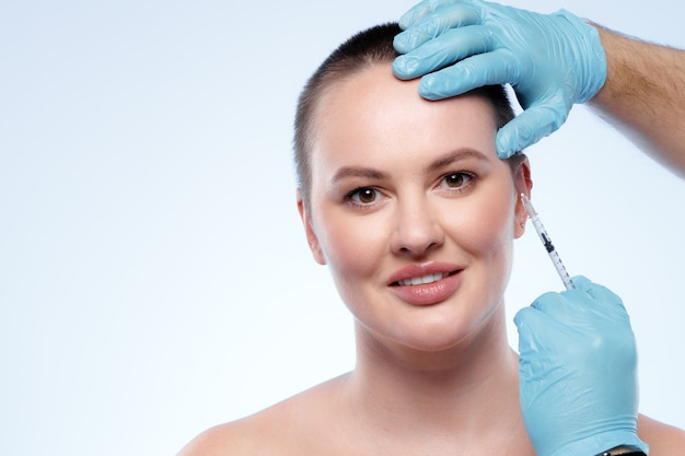 Красавице с короткими волосами делают укол красоты в лицо