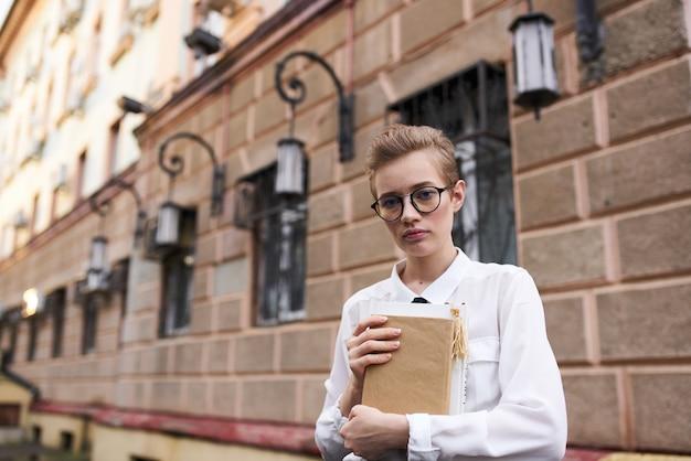 Красивая женщина с короткими волосами держит в руке блокнот и стоит возле кирпичного здания на