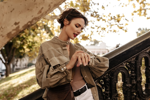 Beautiful woman with short hair in olive jacket looks at watch outdoors. brunette woman with handbag with bright lips poses outside.