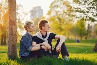 Beautiful woman with short light hair, dressed in a blue jeans jacket sitting with her boyfriend