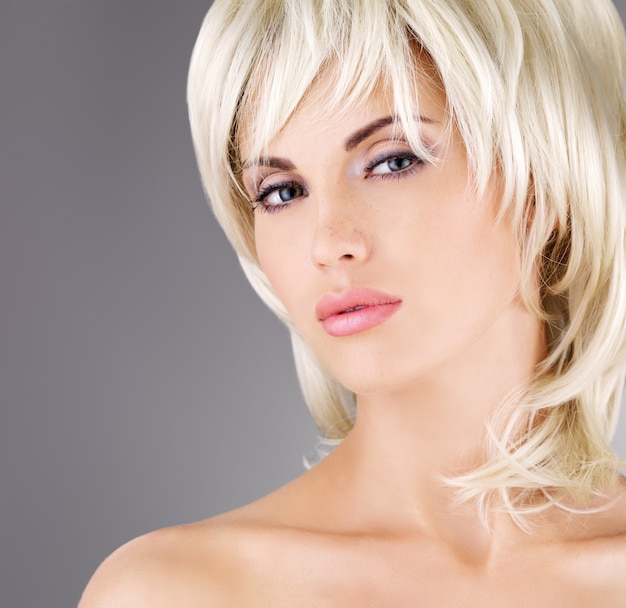 Beautiful woman with shot blond hairstyle, closeup portrait of a female model