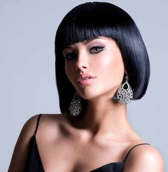 샷된 헤어 스타일과 현대 귀걸이 포즈와 아름 다운 여자