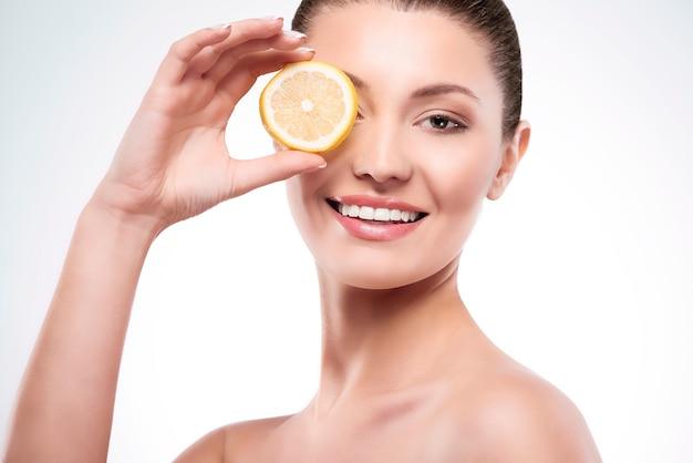 レモンのスライスを持つ美しい女性