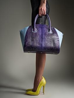 Bella donna con gambe sottili in tacchi alti gialli. la ragazza alla moda tiene la borsa blu alla moda. concetto elegante glamour. arte. la donna cammina dopo lo shopping. femmina irriconoscibile.