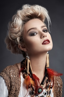 Beautiful woman with smokey eyes make-up and feather earrings and necklace
