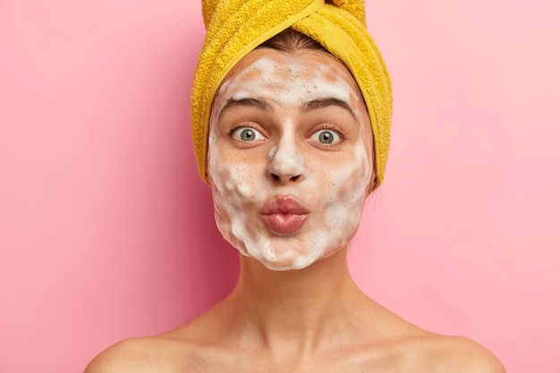 Beautiful woman with soap bubble on face, washes skin, has naked body, wears wrapped towel on head